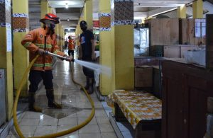 Petugas saat aksi semprotkan cairan disenfektan.